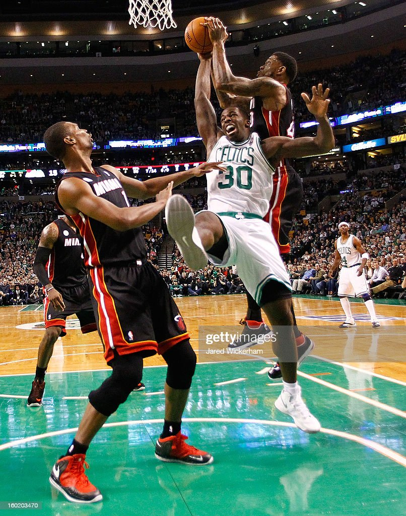 Brandon Bass #30 of the Boston Celtics fights for a loose ball with Udonis Haslem #40 of the Miami Heat during the game on January 27, 2013 at TD Garden in Boston, Massachusetts.