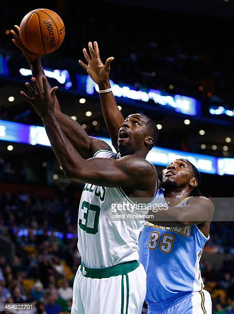 Brandon Bass of the Boston Celtics goes up for a layup in front of Kenneth Faried of the Denver Nuggets in the first quarter during the game at TD...