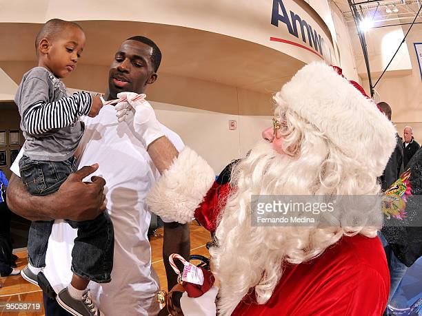 Brandon Bass of the Orlando Magic looks on as Santa Claus hands out a candy cane during a holiday party for 42 families from Apopka Family Learning...
