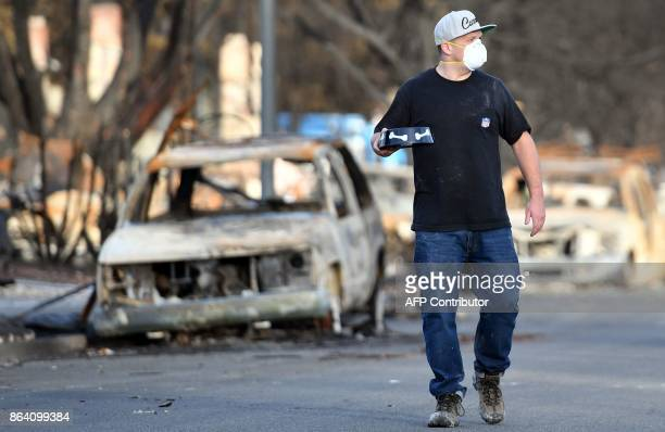 Brandon Bell calls out for his missing cats Pumpkin and Rasta as he walks with a dish of pet food through his burned neighborhood in Santa Rosa...