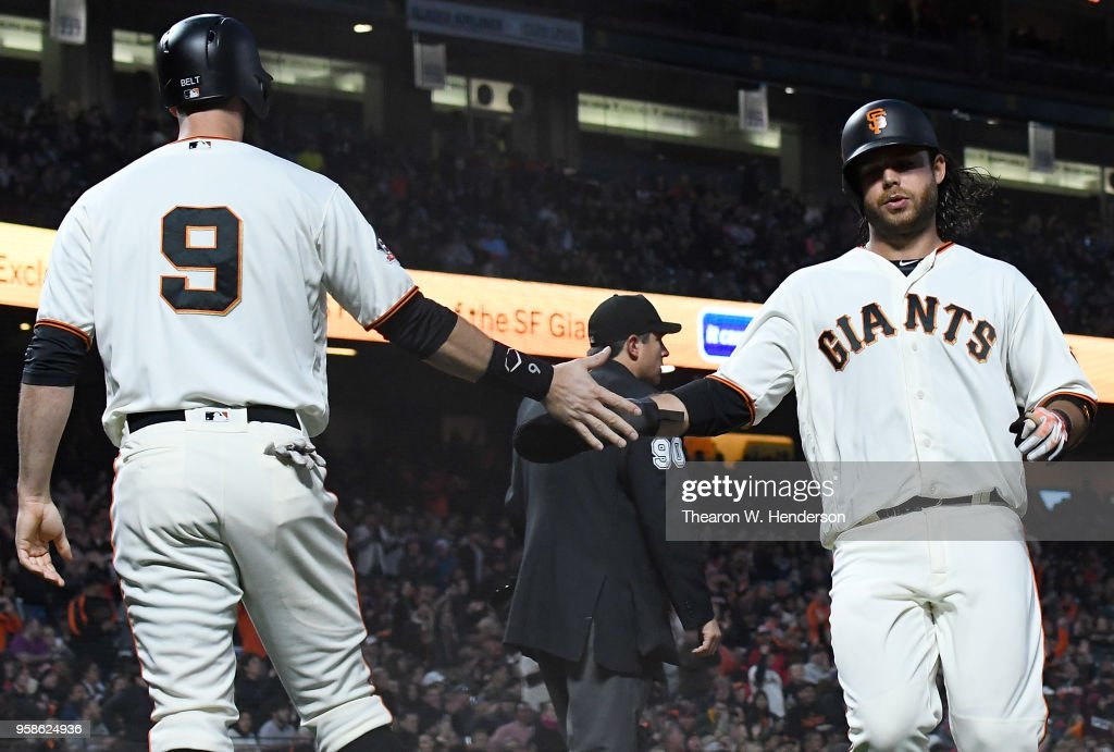 Brandon Belt #9 and Brandon Crawford #35 of the San Francisco Giants slap hands after they both scored on a bases loaded two-run rbi single from Kelby Tomlinson #37 against the Cincinnati Reds in the bottom of the third inning at AT&T Park on May 14, 2018 in San Francisco, California.