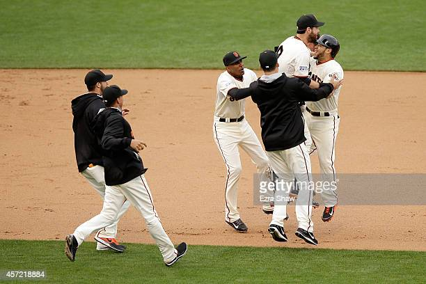 Brandon Belt and Juan Perez of the San Francisco Giants celebrate the 54 10th inning victory against the St Louis Cardinals during Game Three of the...