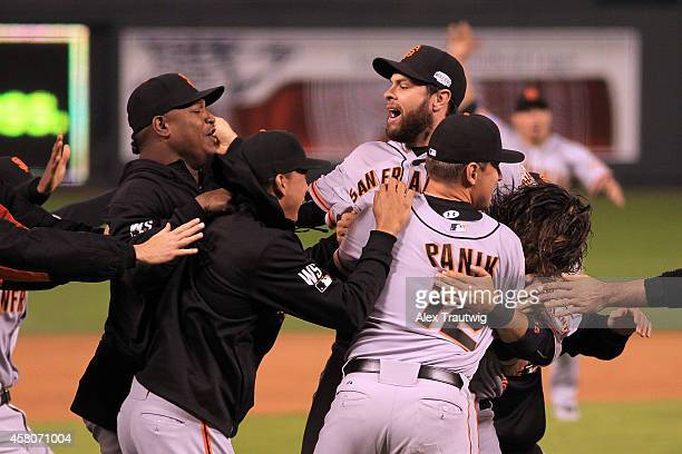 Brandon Belt celebrates with Joe Panik of the San Francisco Giants after defeating the Kansas City Royals 32 in Game Seven of the 2014 World Series...