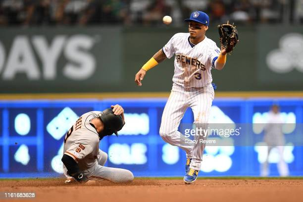 Brandon Belt of the San Francisco Giants beats a tag by Orlando Arcia of the Milwaukee Brewers during the fourth inning at Miller Park on July 12,...