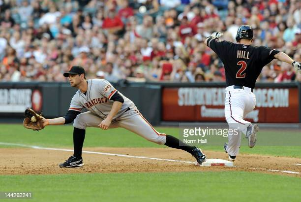 Brandon Belt of the San Francisco Giants catches a throw at first base just ahead of Aaron Hill of the Arizona Diamondbacks at Chase Field on May 12...