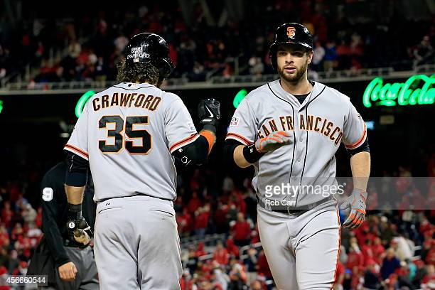 Brandon Belt of the San Francisco Giants celebrates with his teammate Brandon Crawford after hitting a solo home run to right field in the eighteenth...