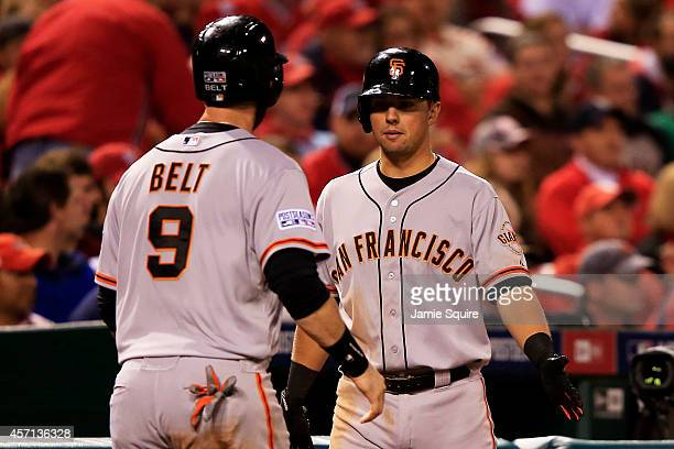 Brandon Belt of the San Francisco Giants celebtrates with Joe Panik after scoring in the fifth inning against the St Louis Cardinals during Game Two...
