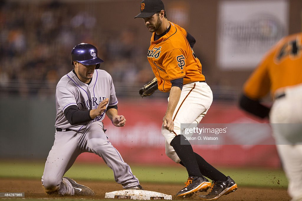 Brandon Belt #9 of the San Francisco Giants completes a double play by forcing out Jordan Pacheco #58 of the Colorado Rockies at first base during the eighth inning at AT&T Park on April 11, 2014 in San Francisco, California.