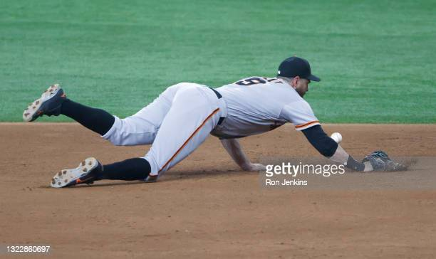 Brandon Belt of the San Francisco Giants dives for a ball off the bat of Isiah Kiner-Falefa of the Texas Rangers during the ninth inning at Globe...