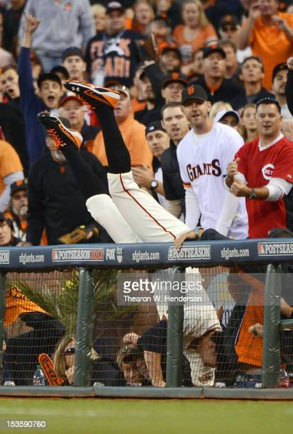 Brandon Belt of the San Francisco Giants flips into the stands after catching a foul popup off the bat of Zach Cozart of the Cincinnati Reds during...