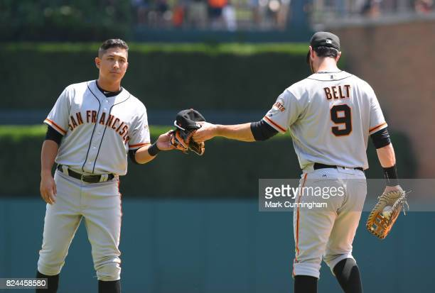 Brandon Belt of the San Francisco Giants hands a baseball hat and glove to teammate JaeGyun Hwang during the game against the Detroit Tigers at...