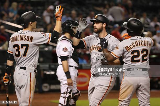 Brandon Belt of the San Francisco Giants high fives Kelby Tomlinson and Andrew McCutchen after hitting a tworun home run against the Arizona...
