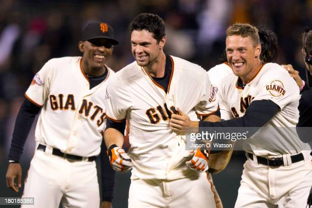 Brandon Belt of the San Francisco Giants is congratulated by Joaquin Arias and Hunter Pence after hitting a walkoff single against the Colorado...