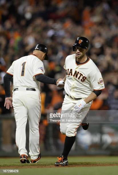 Brandon Belt of the San Francisco Giants is congratulated by third base coach Tim Flannery after he hit a pinch hit tworun home run to tie the game...