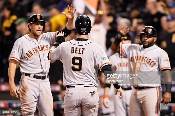 Brandon Belt of the San Francisco Giants is welcomed home as he scores on a fourrun home run hit by Brandon Crawford in the fourth inning against the...