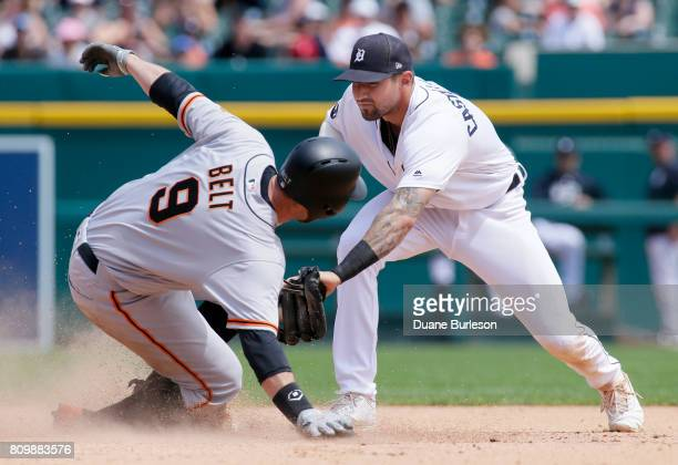 Brandon Belt of the San Francisco Giants makes a hit a double beating the tag from third baseman Nicholas Castellanos of the Detroit Tigers coving at...