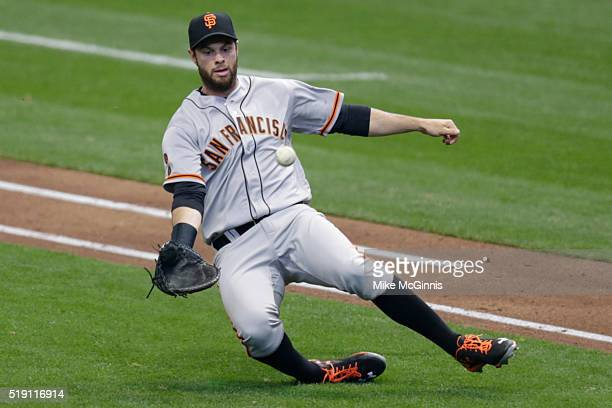 Brandon Belt of the San Francisco Giants makes a sliding catch to retire Wily Peralta of the Milwaukee Brewers during the fourth inningon Opening Day...