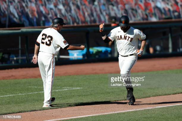 Brandon Belt of the San Francisco Giants rounds the bases after hitting a solo home run in the bottom of the ninth inning against the Colorado...