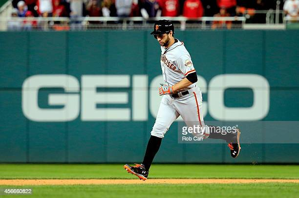 Brandon Belt of the San Francisco Giants runs the bases after hitting a solo home run to right field in the eighteenth inning against Tanner Roark of...