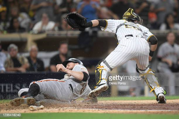 Brandon Belt of the San Francisco Giants scores ahead of a tag by Austin Nola of the San Diego Padres during the ninth inning of a baseball game at...