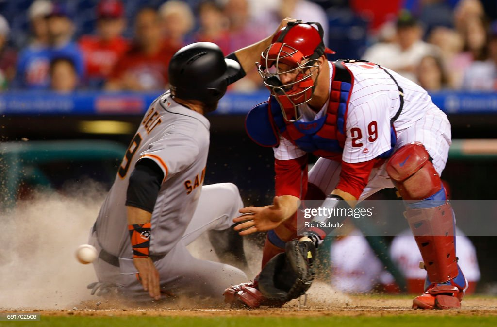 Brandon Belt #9 of the San Francisco Giants scores before catcher Cameron Rupp #29 the Philadelphia Phillies gets the ball on a single by Joe Panik #12 during the ninth inning of a game at Citizens Bank Park on June 2, 2017 in Philadelphia, Pennsylvania. The Giants defeated the Phillies 10-0.