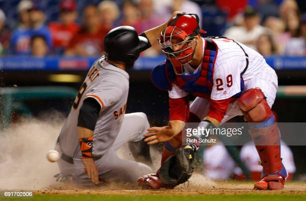 Brandon Belt of the San Francisco Giants scores before catcher Cameron Rupp the Philadelphia Phillies gets the ball on a single by Joe Panik during...