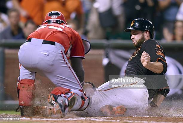 Brandon Belt of the San Francisco Giants scores sliding under the tag of catcher Jose Lobaton of the Washington Nationals in the bottom of the third...