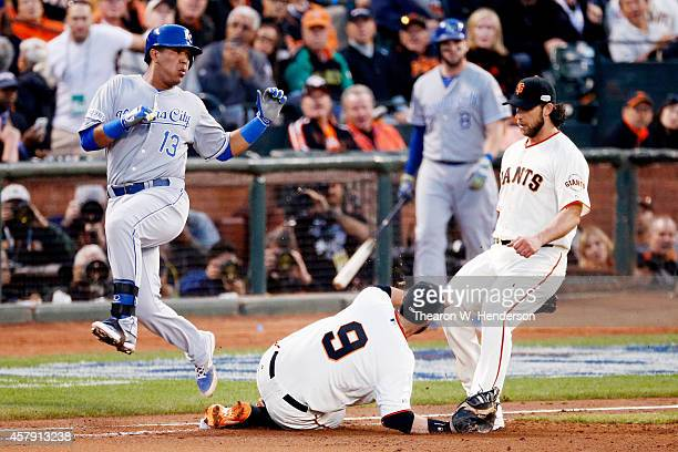 Brandon Belt of the San Francisco Giants slides to make the out against Salvador Perez of the Kansas City Royals in the fourth inning during Game...