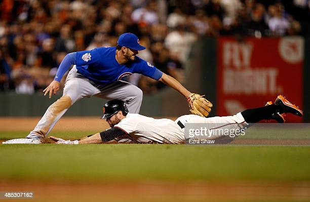 Brandon Belt of the San Francisco Giants slides under the tag of Kris Bryant of the Chicago Cubs for a triple in the sixth inning at ATT Park on...
