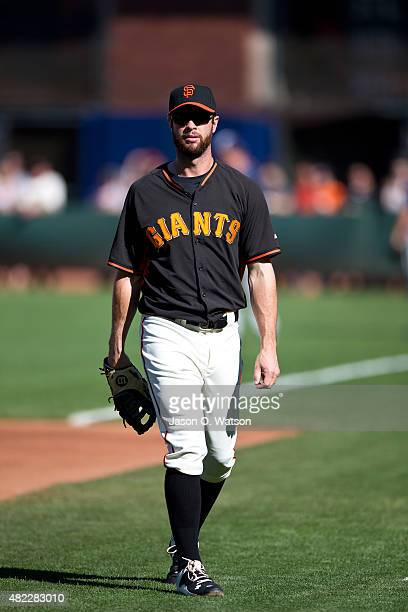 Brandon Belt of the San Francisco Giants walks across the field during batting practice before the game against the Milwaukee Brewers at ATT Park on...