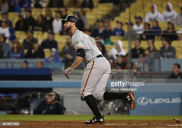 Brandon Belt of the San Francisco Giants watches his fly ball go to deep center field during the ninth inning of the MLB game against the Los Angeles...