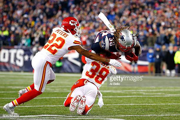 Brandon Bolden of the New England Patriots is tackled by Ron Parker and Marcus Peters of the Kansas City Chiefs in the first half during the AFC...