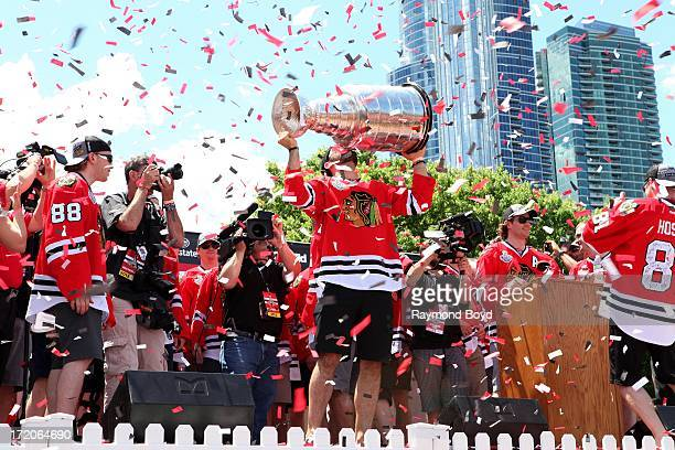 Brandon Bollig forward for the Chicago Blackhawks raises and kisses the Stanley Cup Trophy during the Chicago Blackhawks' 2013 Stanley Cup...