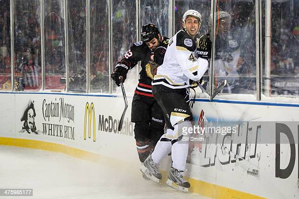 Brandon Bollig of the Chicago Blackhawks and Robert Bortuzzo of the Pittsburgh Penguins get physical by the boards during the 2014 NHL Stadium Series...