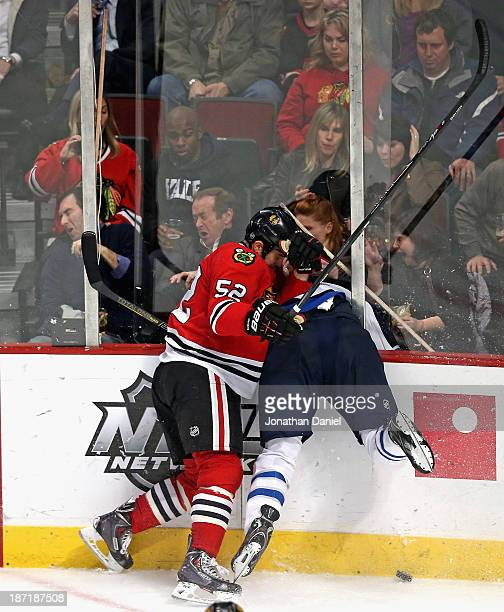 Brandon Bollig of the Chicago Blackhawks checks Adam Pardy of the Winnipeg Jets through the glass at the United Center on November 6 2013 in Chicago...