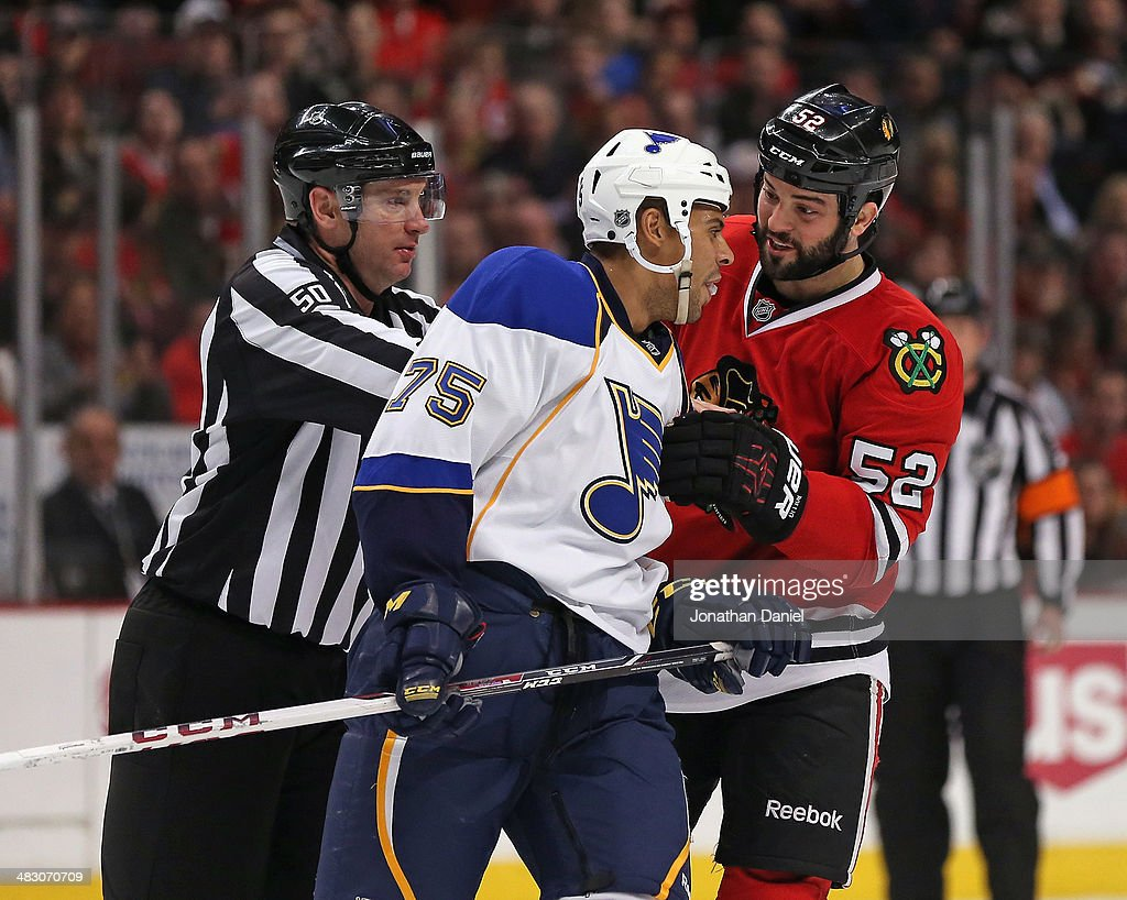Brandon Bollig #52 of the Chicago Blackhawks has words with Ryan Reeves #75 of the St. Louis Blues as liesman Scott Cherrey #50 moves to separate them at the United Center on April 6, 2014 in Chicago, Illinois.