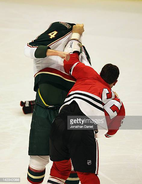Brandon Bollig of the Chicago Blackhawks pulls the jersey of Clayton Stoner of the Minnesota Wild over his head as they fight in the first period at...