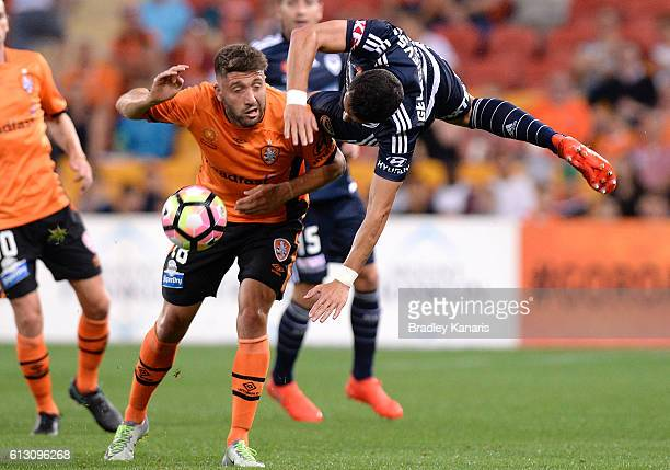 Brandon Borrello of the Roar and Daniel Georgievski of the Victory challenge for the ball during the round one ALeague match between the Brisbane...