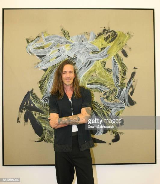Brandon Boyd poses in front of his artwork at OptiMystic A Brandon Boyd Pop Up Gallery Featuring He Tasya Van Ree Natalie Bergman Diana Garcia And DJ...
