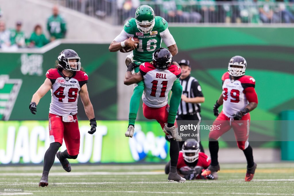 Brandon Bridge #16 of the Saskatchewan Roughriders tries to hurdle Joshua Bell #11 of the Calgary Stampeders after scrambling with the ball in the second half of the game between the Calgary Stampeders and Saskatchewan Roughriders at Mosaic Stadium on September 24, 2017 in Regina, Canada.