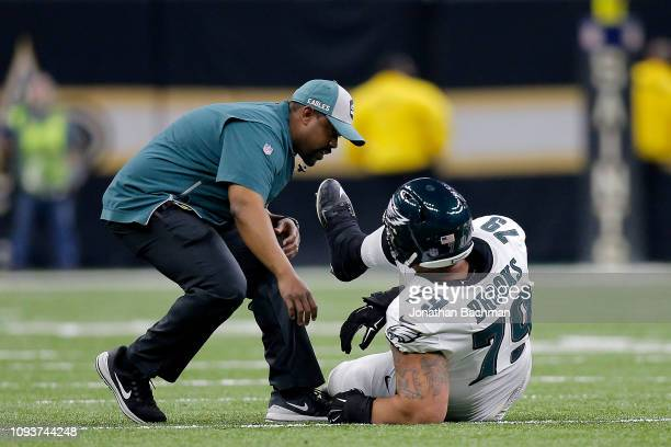 Brandon Brooks of the Philadelphia Eagles is tended to by the trainer after sustaining a second quarter injury against the New Orleans Saints in the...