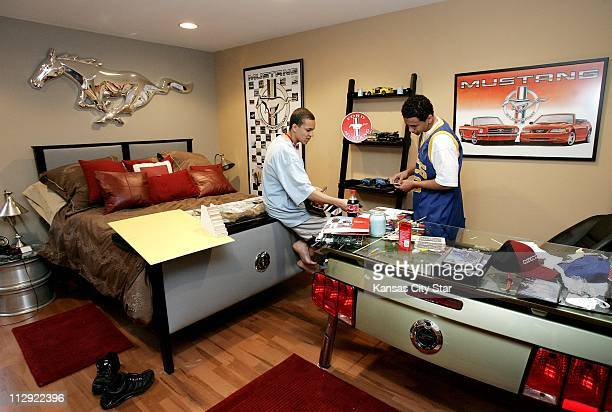 Brandon Brownfield left and Chris Brownfield identify the different cars on the shelf between them by using collector cards in Chris' room March 21...