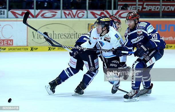Brandon Buck of Ingolstadt is challenged by Jean Philippe Cote and Kevin Lavallee of Iserlohn during the DEL match between Iserlohn Roosters and ERC...