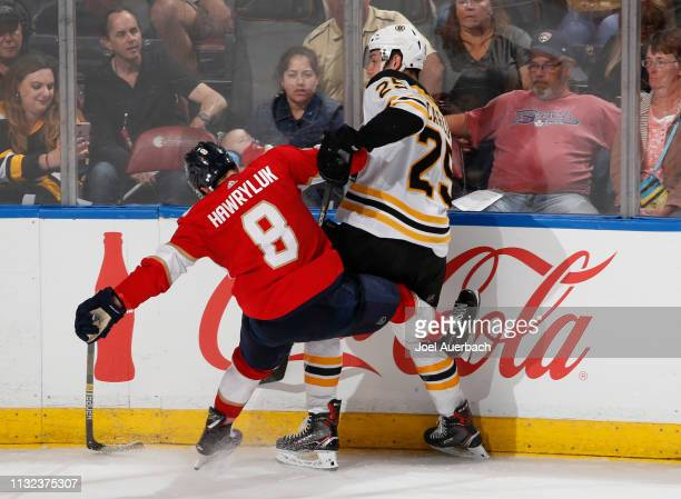 Brandon Carlo of the Boston Bruins and Jayce Hawryluk of the Florida Panthers battle for th epic along the boards at the BBT Center on March 23 2019...