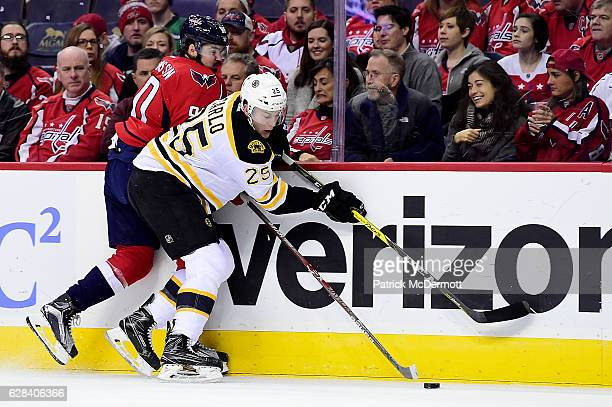 Brandon Carlo of the Boston Bruins and Marcus Johansson of the Washington Capitals battle for the puck in the first period during a NHL game at...