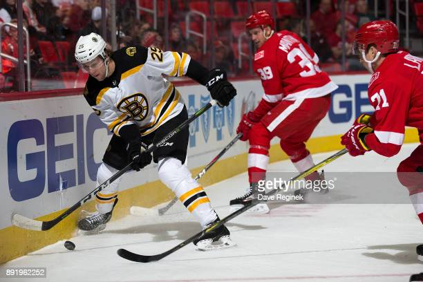 Brandon Carlo of the Boston Bruins battles along the boards for the puck with Dylan Larkin and Anthony Mantha of the Detroit Red Wings during an NHL...