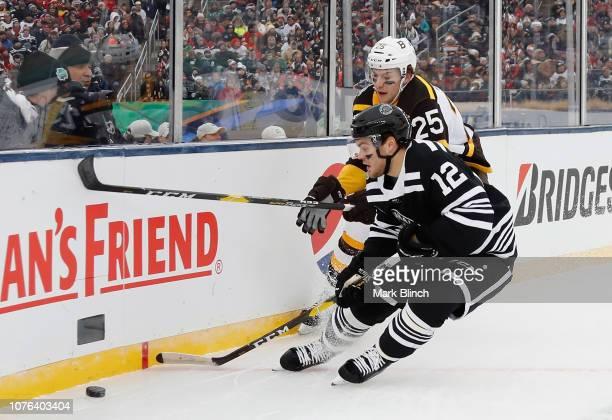Brandon Carlo of the Boston Bruins battles with Alex DeBrincat of the  Chicago Blackhawks during the. 2019 Bridgestone NHL Winter Classic ... 1526135fd