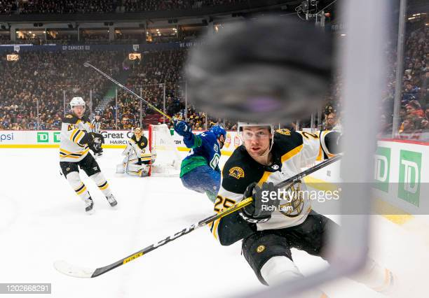 Brandon Carlo of the Boston Bruins chases after the puck after Tyler Motte of the Vancouver Canucks cleared the puck off the glass during NHL action...