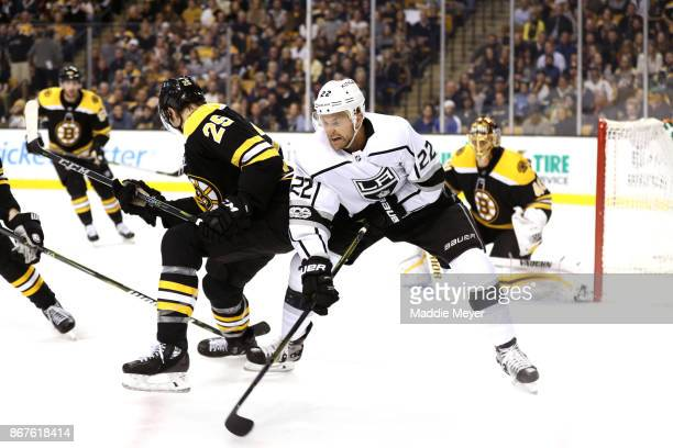 Brandon Carlo of the Boston Bruins defends Trevor Lewis of the Los Angeles Kings during the second period at TD Garden on October 28 2017 in Boston...