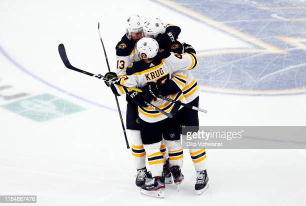 Brandon Carlo of the Boston Bruins is congratulated by his teammates Charlie Coyle and Torey Krug after scoring a third period goal against the St...